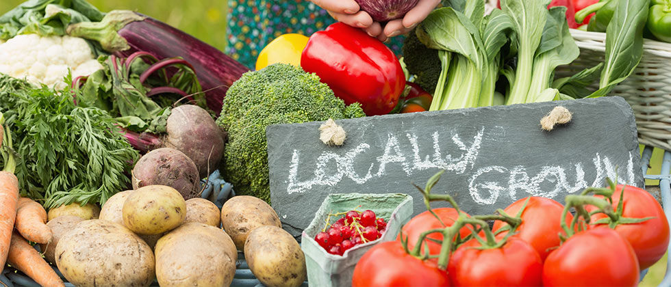 Fresh produce at a farmer's market with a sign that says Locally Grown