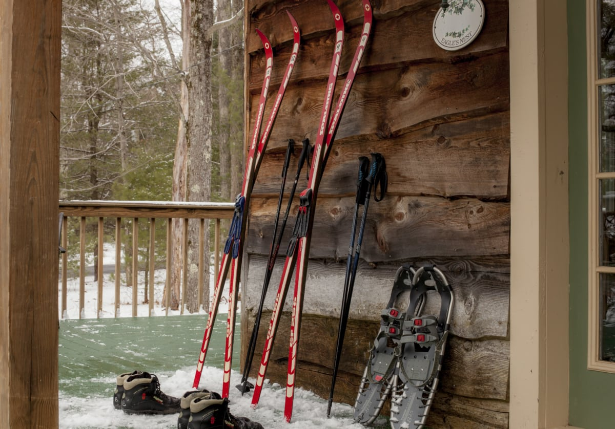 Skis, snowshoes, and boots against a building