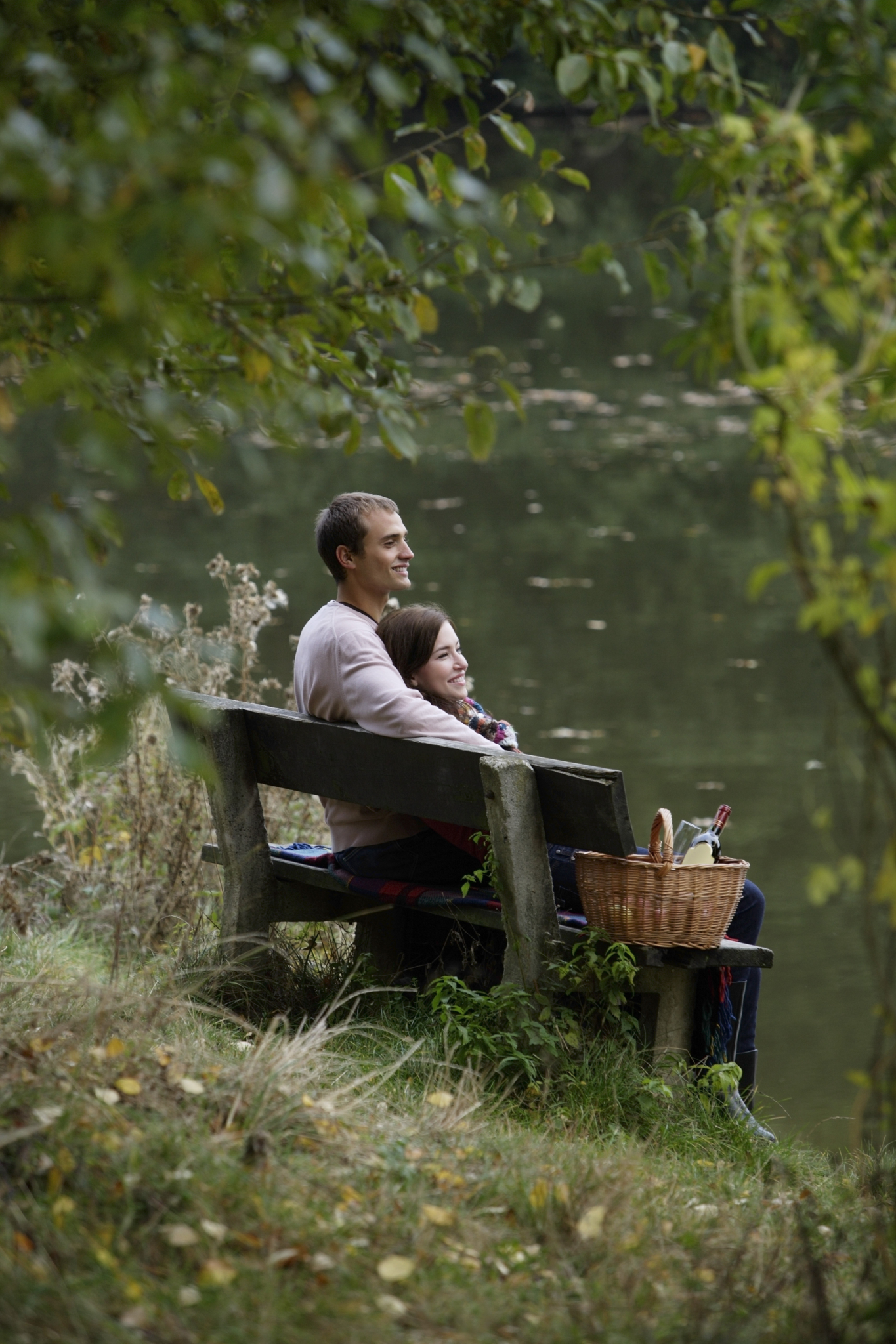 Couple sitting on a bench by the lake