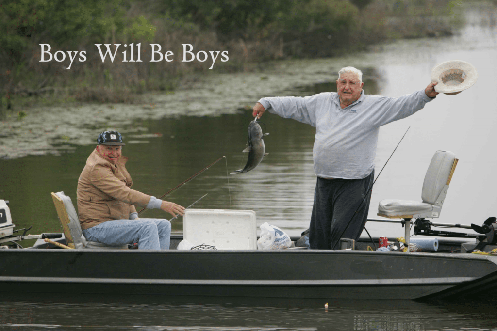 Two men in a fishing boat with overlay text: Boys will be boys