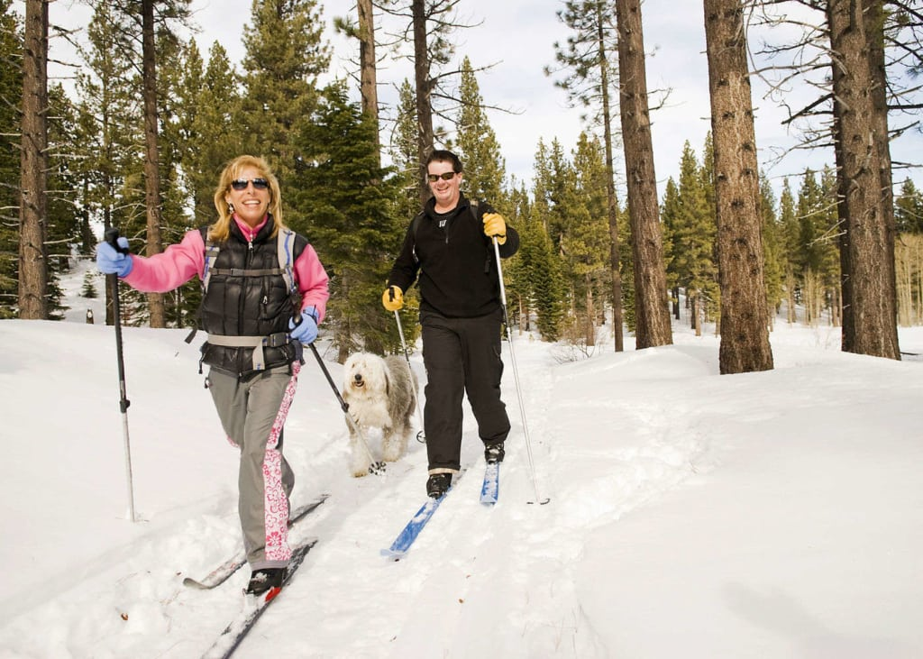 A man and woman on cross-country skis with a dog running behind them