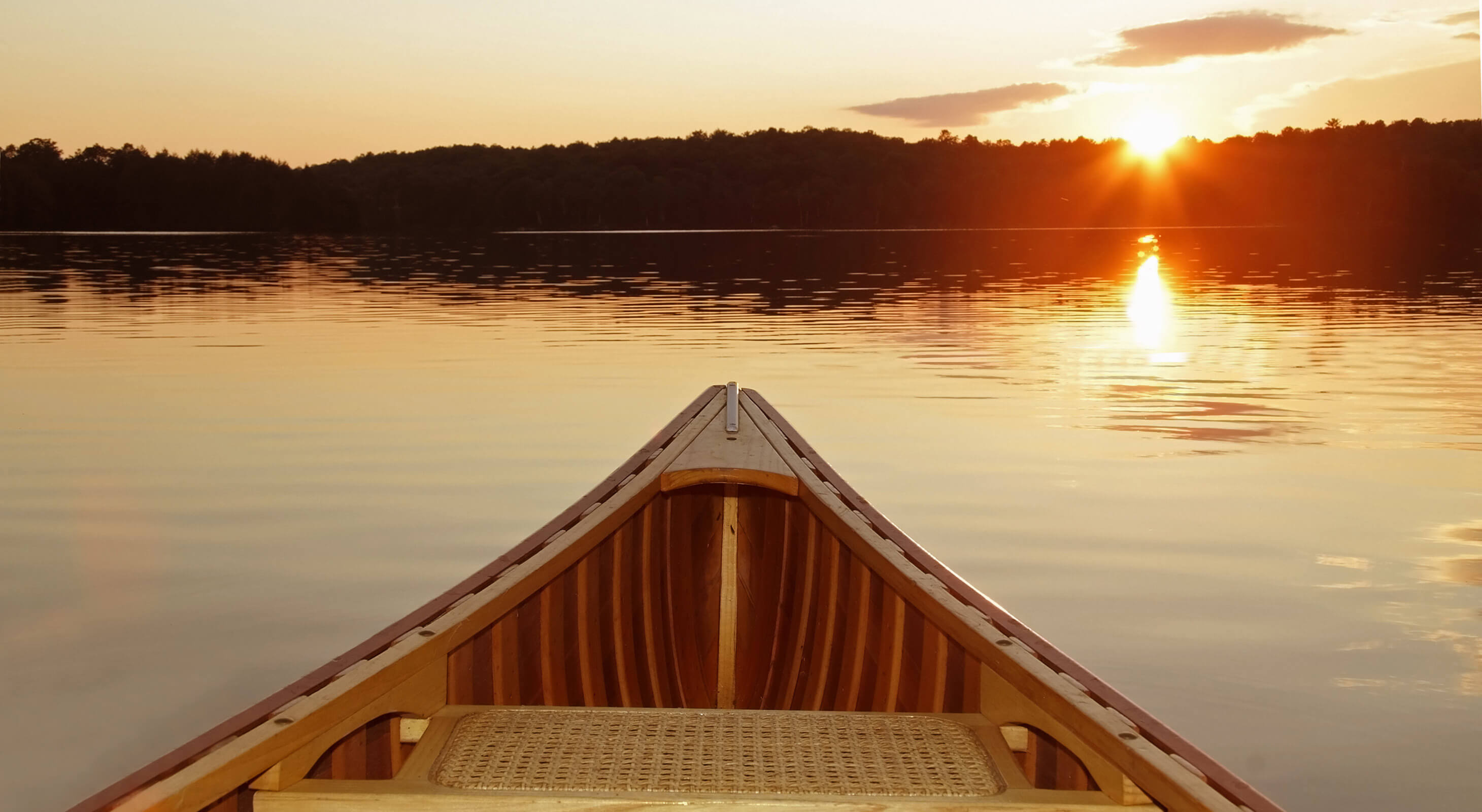 Canoe on water at sunset