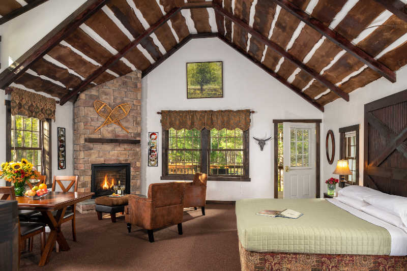 Guest room with bed, vaulted ceilings, fireplace at NY Inn