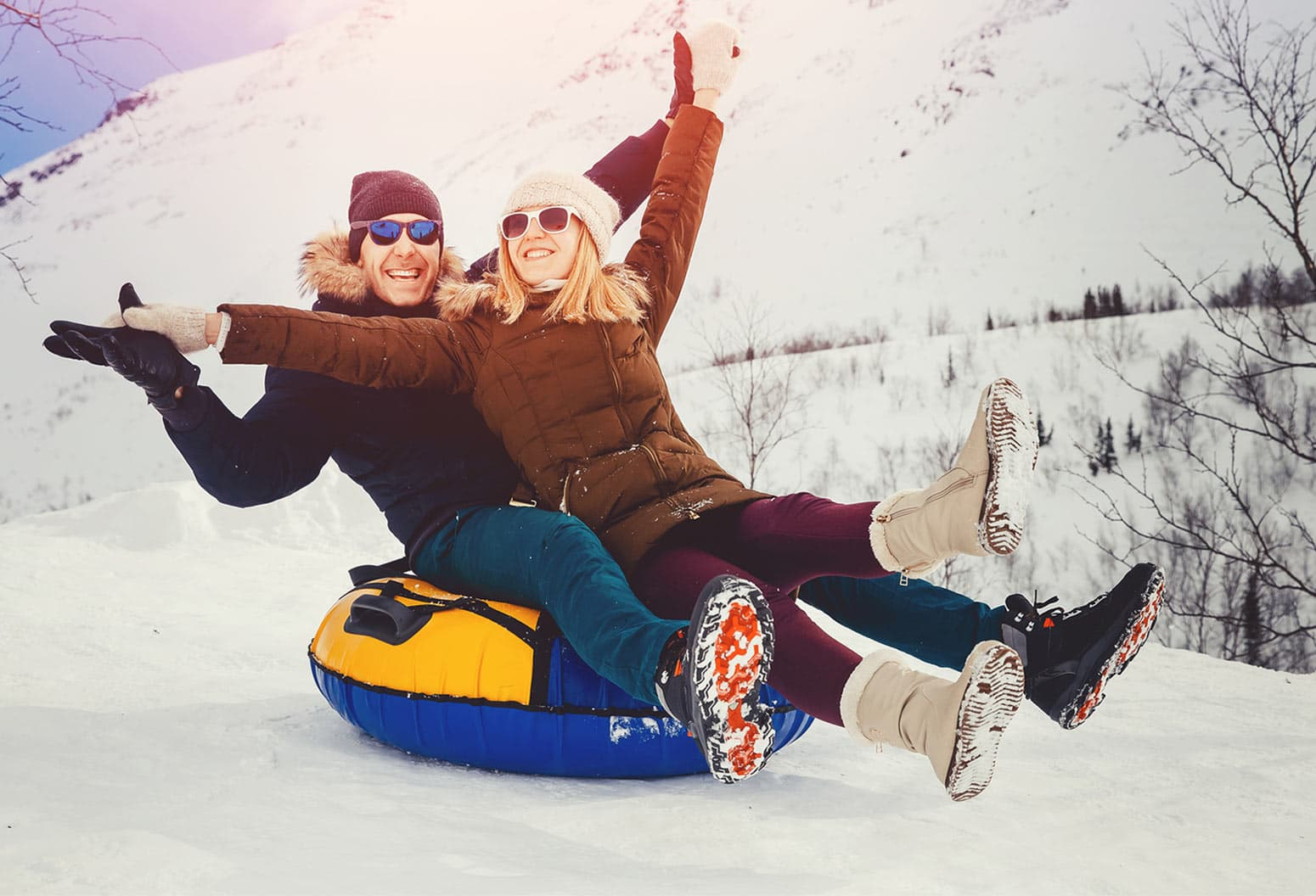 Couple in winter going downhill on a tube