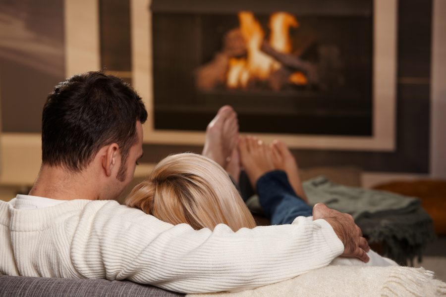 a couple sitting by a fireplace